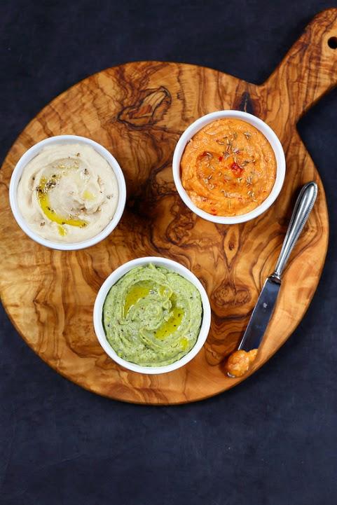 Houmous de haricots tarbais en trilogie : harissa, pesto de pistaches et sésame