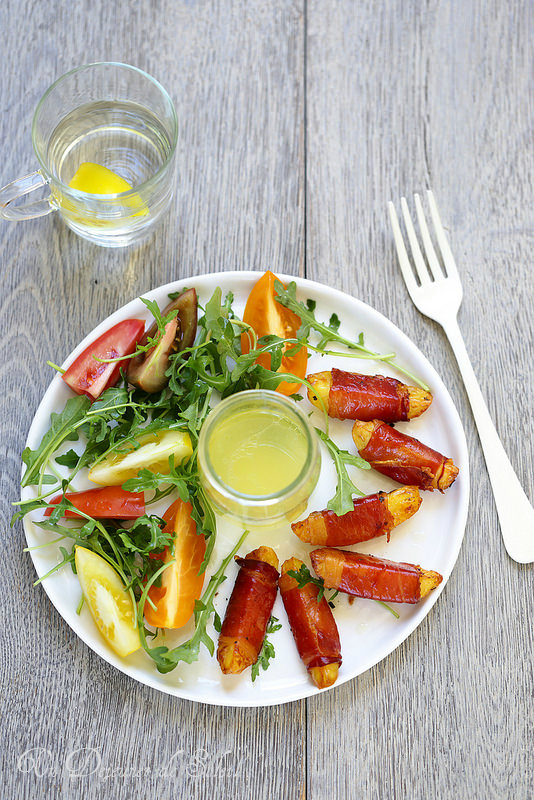 Salade de pommes de terres rôties enrobées speck, avec des tomates et de la roquette
